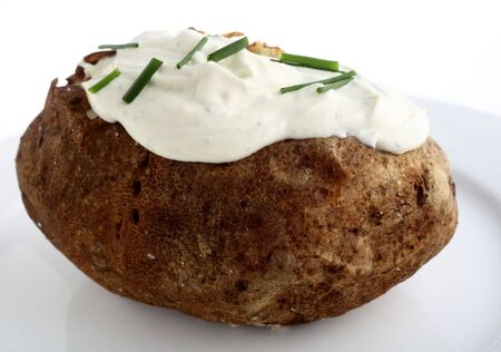 russet potato: A baked Russet potato topped with a cream cheese and chives mixture Stock Photo