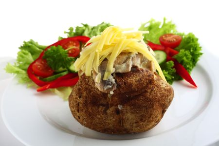 A baked potato topped with a mushroom sauce and grated cheddar cheese, served with a salad Stock Photo - 6366997