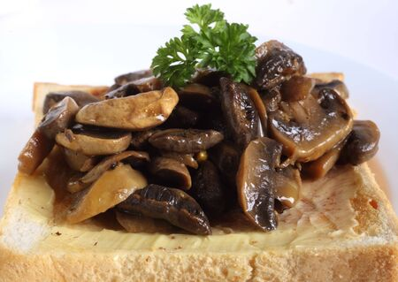 sauteed: Sauteed mushrooms, topped with a sprig of parsley, on a slice of buttered toast