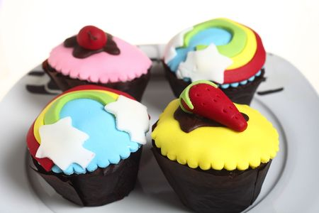 cake decorating: Four highly decorated cupcakes on a plate, ideal for a childrens party.