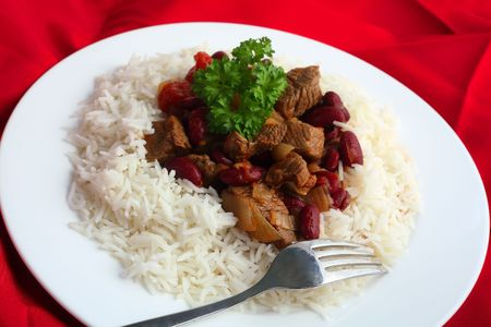 chili con carne on rice, topped with a sprig of parsley with a fork on a red cloth. photo