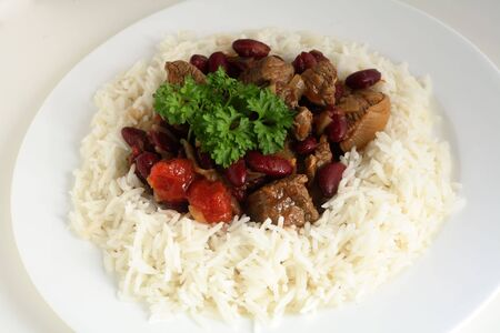 basmati: A plate of chilli con carne with rice over a white background