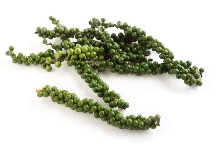 A drupe of green peppercorns from the vine, over white with a light shadow. These are the peppers from which black pepper is made and they are also used green in some asian cookery
