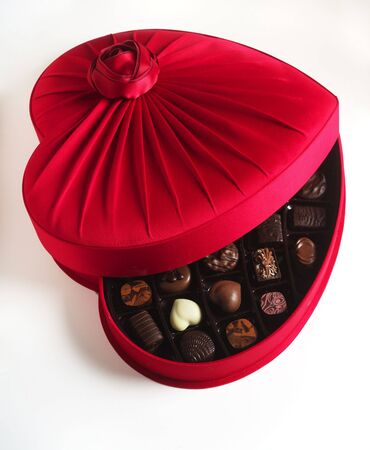 box of chocolates: An opened red heart-shaped box of luxury chocolates