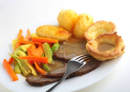 courgettes: Close-up, slanted view of slices of roast beef with yorkshire pudding, roasted potatoes and sauteed carrots and courgettes, topped with a rich gravy Stock Photo