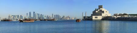 A panoramic view of the skyline of Doha, seen from the corniche with moored dhows and the Museum of Islamic art in the foreground Stock Photo - 6650150