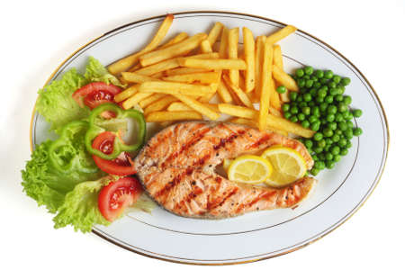 A view of a grilled salmon steak meal served with salad, chips, peas and lemon slices. Stock Photo - 6859475