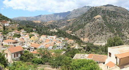 supposedly: A wide angle view of the ancient mountain village of Argiroupolis, Crete, supposedly founded by Agamemnon and known in Roman times as Lappa, with the towering heights of Omanite and Fourni behind. The village water supply still comes from cisterns built o Archivio Fotografico