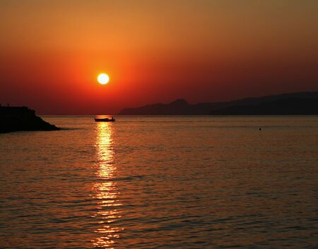 The sun rises over the hills beyond Agios Nikolaos on Crete, Greece, while a lone fisherman makes his way back to harbour with the nights catch.
