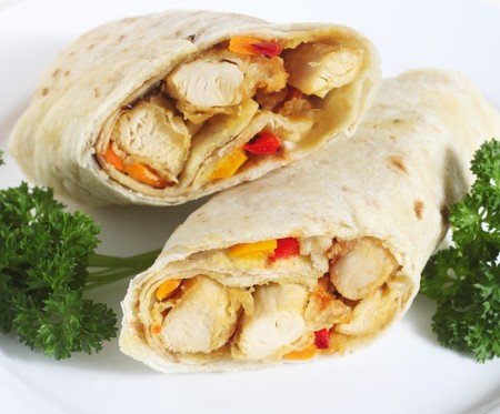 Chicken fajita sandwiches, wrapped in a tortilla, and served with a garnish of fresh parsley photo