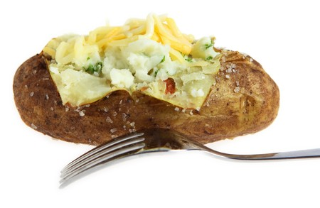 A baked potato crusted with sea-salt, filled with creamed mashed parsley potato and topped with grated cheese, with a fork, isolated over white Stock Photo