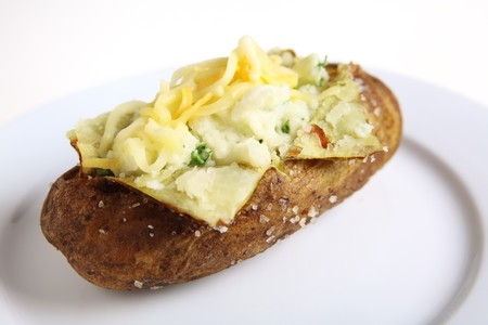 A baked burbank russet or Idaho potato, filled with parsley creamed potato and topped with grated cheese, on a white plate providing space for text Stock Photo - 7649004