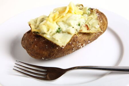 A baked potato stuffed with creamed parsley potato and topped with grated cheese on a white plate with a fork Stock Photo - 7649006
