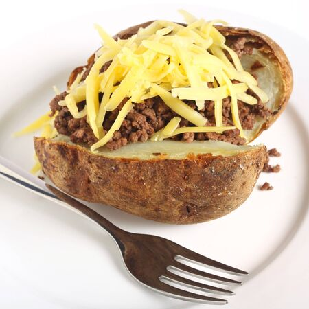 russet potato: A baked russet burbank (or Idaho) potato stuffed with minced beef topped with cheese. Stock Photo