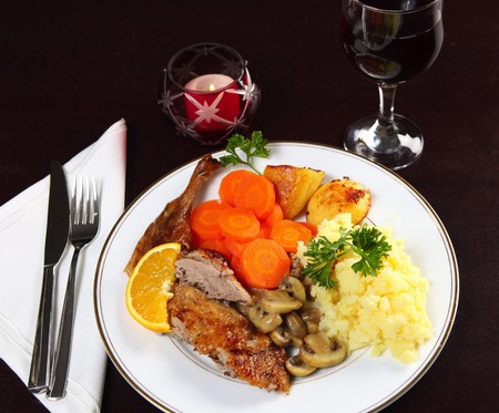 candlelit: A romantic candle-lit dinner of roast duck, potatoes, mushrooms and carrots on a dark wooden table.