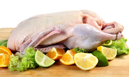 A raw duck on a chopping board, with segments of lemon, orange and lime and lettuce leaves.