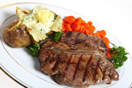 A dinner of a T-bone or porterhouse steak, served with baked potato with creamed parsley potato filling and boiled carrots, garnished with English parsley