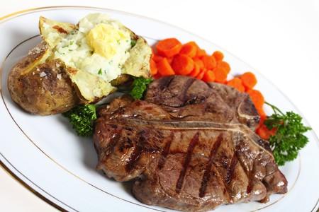 Una cena de un t-Bone o steak porterhouse, servido con papa asada con crema de perejil de patatas de llenado y cocido de zanahorias, adornadas con perejil inglés