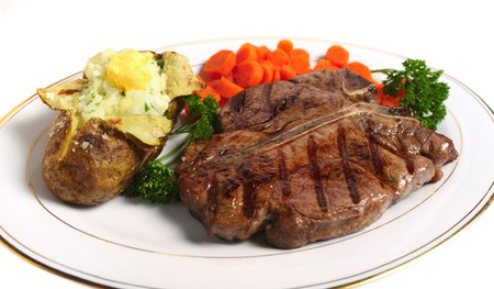 steak plate: A porterhouse (or T-bone) steak served with baked potato and boiled carrots, viewed from above Stock Photo