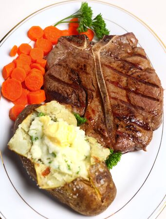 steak dinner: A porterhouse (or T-bone) steak served with baked potato and boiled carrots, viewed from above Stock Photo