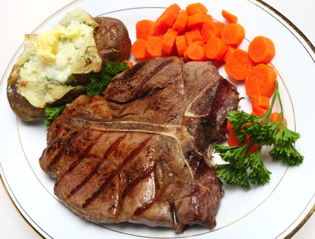 t bone: A porterhouse (or T-bone) steak served with baked potato and boiled carrots, viewed from above Stock Photo