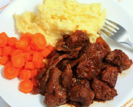 tomato paste: A meal of boeuf bourguignonne french beef stew, viewed from above. This traditional French dish is made with onions, wine, tomato paste, garlic and bacon