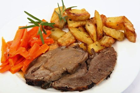 Slices of roast leg of lamb served with gravy, oven-roasted potato wedges and julienned garlic carrots and garnished with rosemary Stock Photo