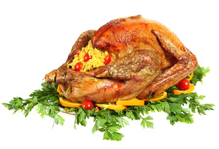 A festive or thanksgiving turkey on a bed of italian flat-leaf parsley, garnished with slices of orange and cherry tomatoes and stuffed with rice photo