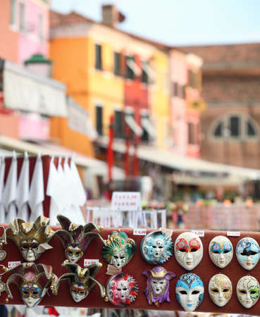 carnevale: Miniature Venetian carnevale masks on sale on Burano island, which is part of the Venetian archipelago. The islands iconic colourfully painted buildings are out of focus in the background Stock Photo