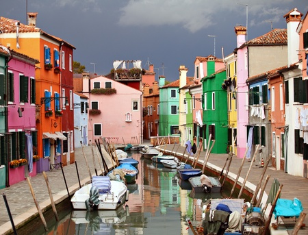 canal house: The already fantastic colours of houses in Burano, one of the Venetian islands, acquire incredible vibrance as an autumn thunderstorm threatens.