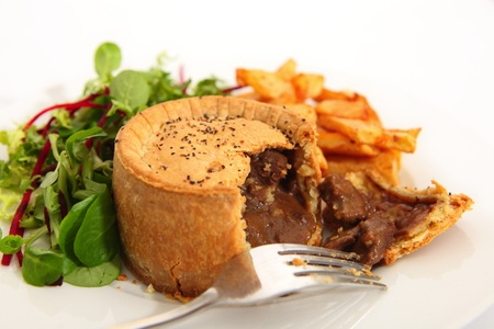 A raised steak pie, served with french fried potato chips and a green salad. photo