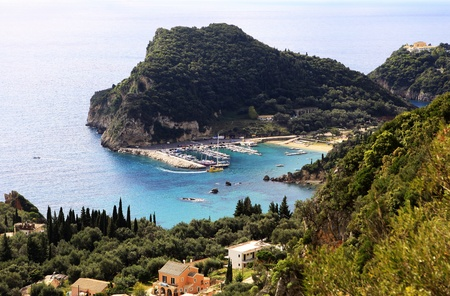 tourist attractions: View from the mountain above of Paleokastritsa harbour, Corfu, with Paleokastritsa monastery top right. The sandy bays are among the Ionian islands top tourist attractions,