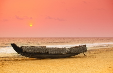 The sun sets behind a beached traditional Kerala, India, fishing boat. The boat has been covered with coconut palm thatch as a protection against the weather. photo