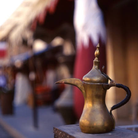 coffeepot: A coffee pot - the Arab symbol of welcome - in front of a Qatari flag in Souq Waqif, Doha, Qatar. The souq is one of Qatars main tourist attractions. Stock Photo