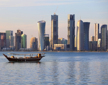 A dhow returns to harbour in Doha, Qatar, at sunset, with the citys modern skyline in the background.