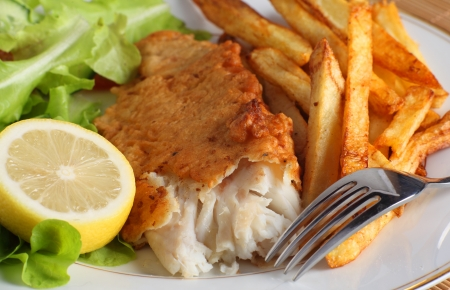 A dinner of fish and chips (or french fries) served with a salad of garden-fresh lettuce, rocket and tomato and a piece of lemon photo