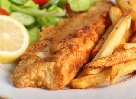 A piece of fish in batter served with french fried potato chips, lemon and a lettuce, rocket, cucumber and tomato salad. photo