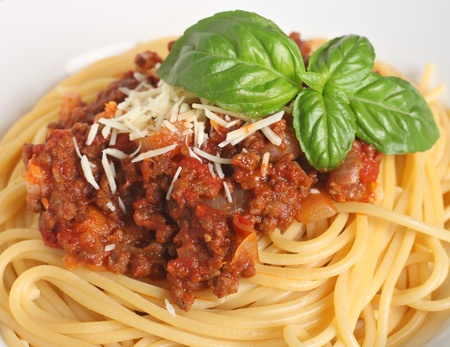 spaghetti sauce: Close-up view of a plate of spaghetti bolognese, garnished with a sprig of Italian, large-leafed basil