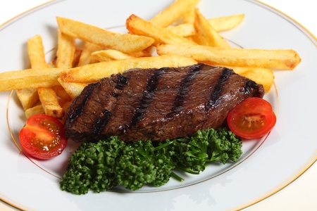 steak dinner: Steak and chips, garnished with cherry tomatoes and curly parsley