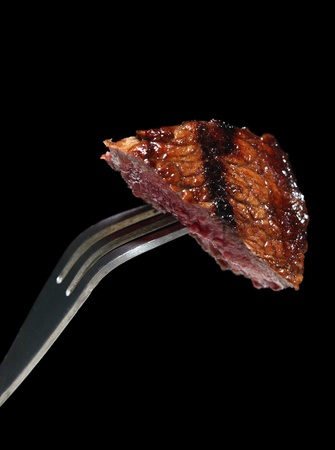 A grilled piece of rump steak on a steak fork over a black background.