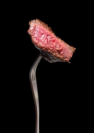 sirloin steak: A piece of grilled steak on a fork, isolated on black.