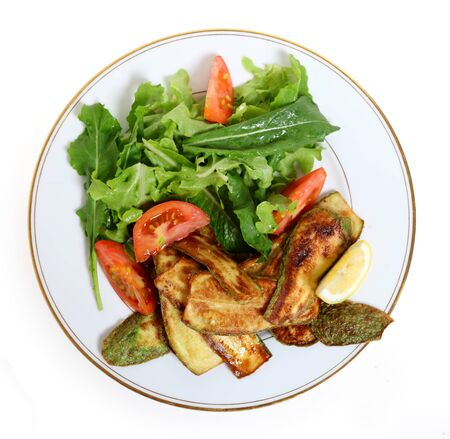 roquette: High-angle view of a vegan meal of fried courgette slices and a salad of rocket (roquette), tomato and lettuce, served with a wedge of lemon