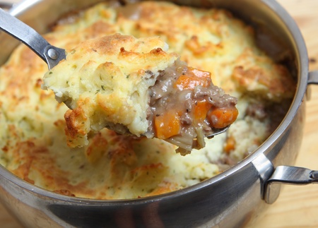A serving spoon full of shepherds pie (minced meat and vegetable stew topped with mashed potatoes baked to a golden crust) over the cooking pot.