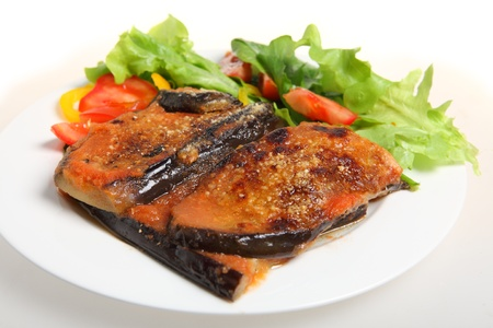 A meal of eggplant parmigiana (eggplant baked with tomato passata and parmisan) with a salad of lettuce, rocket, capsicum and tomato Stock Photo