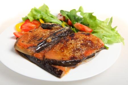 Una comida de berenjena parmigiana (berenjenas al horno con tomate passata y parmisan) con una ensalada de lechuga, tomate, cohetes y capsicum