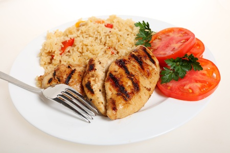 A meal of spicy grilled cajun chicken breasts with vegetable rice and fresh tomato