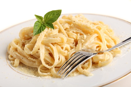 A plate of Fettucine allAlfredo, pasta in a butter, cream and parmesan sauce, garnished with a sprig of basil and sprinkled with grated cheese Stock Photo
