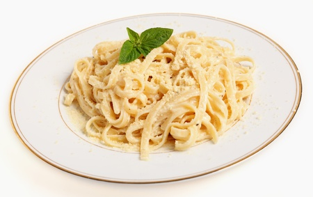 A plate of Fettucine all'Alfredo, pasta in a butter, cream and parmesan sauce, garnished with a sprig of basil and sprinkled with grated cheese Stock Photo - 9146701