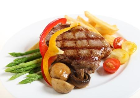 vlees: Gourmet stijl kalfsvlees sirloin steak, opgediend met asperges, gegrilde champignons, cherry tomaten, linten van rode en gele paprika en frietjes. Stockfoto