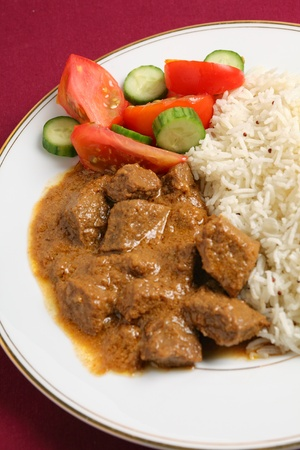 North Indian-style beef korma curry with basmati rice and a salad of tomato and cucumber
